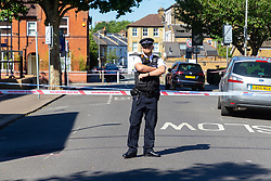 A police officer mans the cordon at the scene where a man in his 40s was stabbed on Latchmere Road in Battersea in the afternoon of July 3rd 2019, dying later that evening in hospital.. London, July 04 2019.