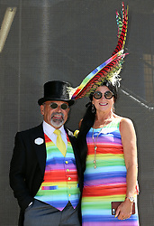 Brian Mann (left) and Rebecca Johnson wearing multicoloured outfits during day three of Royal Ascot at Ascot Racecourse.