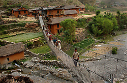 "RUKUM DISTRICT, NEPAL, APRIL 15, 2004:  Nepalese cross a bridge controlled by Maoists in Rukum district April 15, 2004. The infrastructure of Western Nepal is nonexistant and government troops have a hard time manoevering through the difficult terrain to combat the growing Maoist insurgency. Analysts and diplomats estimate there about 15,000-20,000 hard-core Maoist fighters, including many women, backed by 50,000 ""militia"".  In their remote strongholds, they collect taxes and have set up civil administrations, and ""people's courts"" to settle rows. They also raise money by taxing villagers and foreign trekkers. Though young, they are fearsome fighters and  specialise in night attacks and hit-and-run raids. They are tough in Nepal's rugged terrain, full of thick forests and deep ravines and the 150,000 government soldiers are not enough to combat this growing movement that models itself after the Shining Path of Peru. (Ami Vitale/Getty Images)"