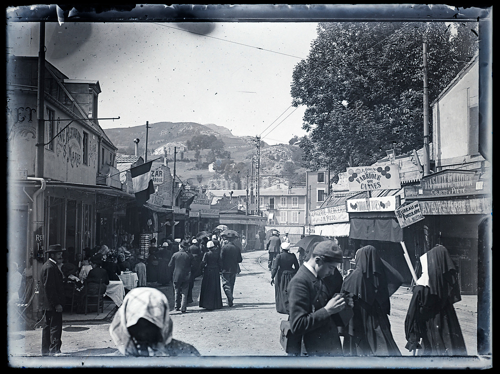 small town shopping street with people walking France ca 1920s
