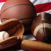 A studio shot of an American Football, a basketball and a baseball ball, mitt and bat on an American flag. 17th October 2012. Photo Tim Clayton