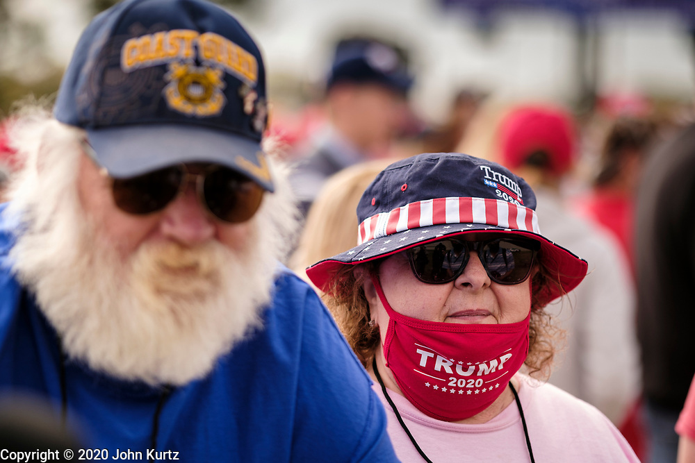 14 OCTOBER 2020 - DES MOINES, IOWA: A woman waits get into a campaign rally for President Donald Trump. About10,000 people were expected at the Des Moines International Airport for a campaign rally supporting the reelection of President Trump. Trump spoke at the rally, despite testing positive for COVID-19 less than three weeks ago. The rally did not meet the CDC guidelines for a safe gathering in the time of Coronavirus and violated Iowa's health emergency declarations barring gatherings of more than 25 people. This week Iowa exceeded 101,000 cases of COVID-19 and a surge in hospitalizations for COVID-19.       PHOTO BY JACK KURTZ