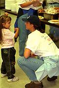 Volunteer talking with kid at Sharing & Caring Hands soup kitchen.  Minneapolis Minnesota USA