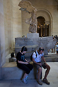 Tourists listen to audio guided tour commentary using free Nintendos beneath the statue of Nike, the ancient Greek Godess of Victory in the Louvre, Paris.