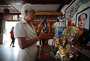 Tang Ruiren, founder of Mao's Family Restaurant chain, shows off some Mao souvenirs in one of her restaurants near the birthplace of Mao Zedong, in Shaoshan, Hunan Province, China on 12 August 2009.  The village of Shaoshan, in rural Hunan Province, is tiny in size but big in name. It was the childhood home for Mao Zedong, the controversial revolutionary who came from obscurity but eventually defied all odds conquered China in the name of communism. Now his home, a sacred place among China's official propaganda, is in reality a microcosm of the country itself: part commercialism, part superstition, with a dash of communist ideological flavor.
