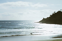Surfer heading out into the water in Pacific City, OR.