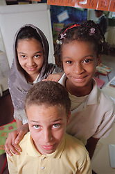 Multiracial group of primary school children standing together in classroom,