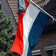 Nederlandse vlag met een schooltas van een geslaagde