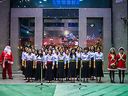 24 DECEMBER 2012 - BANGKOK, THAILAND: Christmas carolers perform for tourists in front of the Windsor Suites Hotel on Sukhumvit Soi 20 in Bangkok. Thailand, a predominantly Buddhist country, has a spirited Christmas season, influenced by the large number of ex-patriots that live in Thailand and tourists who visit Thailand.      PHOTO BY JACK KURTZ