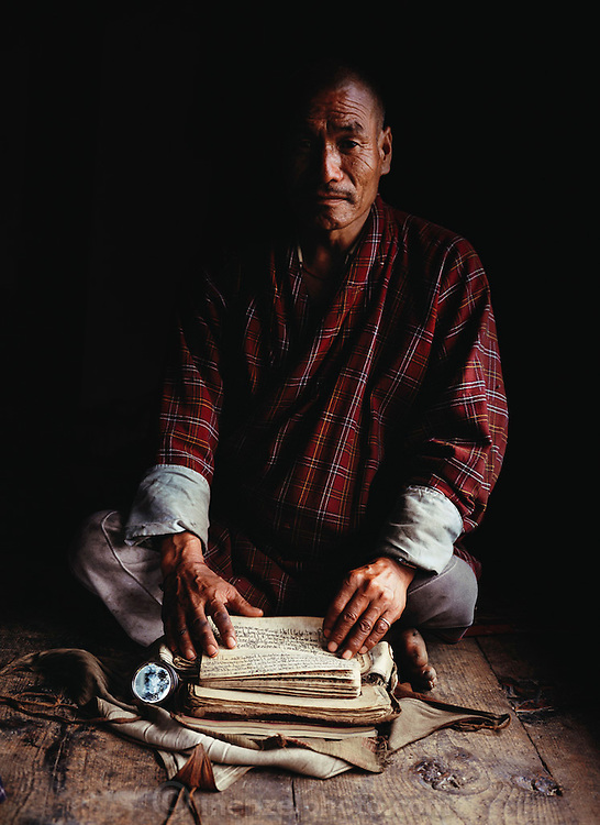 Namgay with his holy texts in the prayer room of his rammed earth house, Shingkhey Village, Bhutan. Namgay, who has a hunched back and a clubfoot, grinds grain for neighbors with a small mill his family purchased from the government.  Namgay is also a reader of sacred texts and conducts house cleansing and healing ceremonies for their 14-house village. From Peter Menzel's Material World Project.