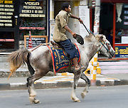 A man rides a horse down the main street of Lakeside, in Pokhara, Nepal.