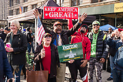 """New York, NY - 11 November 2019. New York City's Veterans Day Parade, today marking the 100th anniversary of the armistice ending the fighting of the first World War, was attended by a number of people protesting President Trump, who spoke at the opening ceremony, and a smaller number of pro-Trump supporters. A woman holding a sign that reads """"Bernie Montpelier VT - 5-25-2019"""" stands in front of three African-American men, one of whom holds high a sign that reads """"Keep America Great."""""""