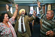 Local residents dancing during a multi faith party at the Neighbourly Care day centre in Southall.