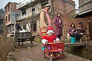 A young mother pushes her son on a walker through a rural village in Shangrao, Jiangxi Province, China on 12 December 2012.   The villages near the city of Shangrao are known for openly defying China's one child policy as most families have more than one child.