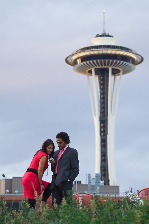 A couple stands at the Seattle Art Museum Olympic Sculpture Park in Seattle, Washington, with the Space Needle rising above them.