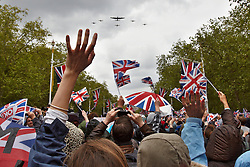 Licensed to London News Pictures. 05/06/2012. LONDON, UK. Spectators wave flags on the Mall during a fly past of WWII aircraft. Great Britain is celebrating the 60th  anniversary of the countries Monarch HRH Queen Elizabeth II accession to the throne this weekend Photo credit : Cliff Hide/ LNP