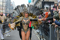 © Licensed to London News Pictures. 01/01/2020. London, UK. A performer from London School of Samba give high five to the members of public during the London New Year's Day Parade in central London. Over 10,000 performers representing the London boroughs and countries from across the globe are parading from Piccadilly Circus to Parliament Square as tens of thousands of Londoners and tourists line the route. Every year, dancers, acrobats, cheerleaders, marching bands, historic vehicles and more assemble in the heart of the capital for a colourful celebration of contemporary performances and traditional pomp and ceremony. Photo credit: Dinendra Haria/LNP