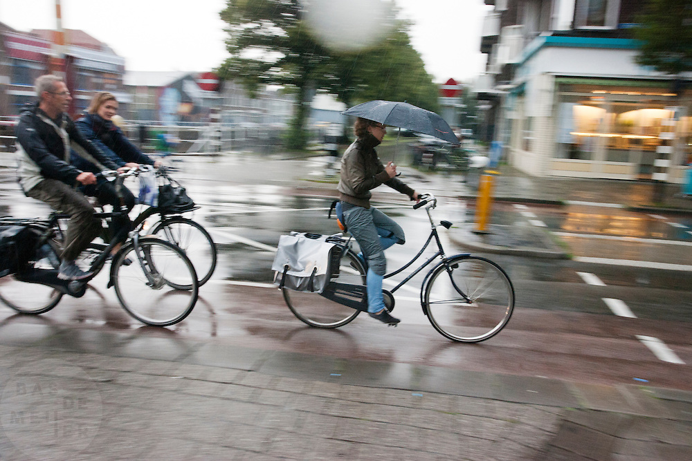 Fietsers rijden door de stromende regen door Utrecht.<br /> <br /> Cyclists in the pouring rain in Utrecht.