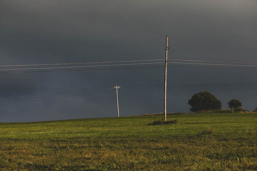 Power lines strung across a rural Vermont farm with stormy skies behind the vista.