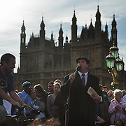 Mark Thomas, political stand-up comedia performing on Westminster Bridge. The amp and speaker is powered by bicycle..The Health and Care Bill has been passed by Parliament and is due to go to the House of Lords. In protest against the bill which aim to deconstruct and privatise large parts of the NHS UK Uncut activists together with health workers and trade unionists blocked the Westminster Bridge from 1pm til 5.30pm.