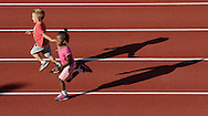 Noah Freestone, 3, and Tyierah Cook, 5, warm up on the Middletown High School track before during the Twilight Track and Field Series on Tuesday, July 30, 2013.