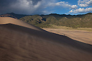 Hikers are dwarfed by the size of the Great Sand Dunes as they hike out of the dune field, with wind blowing sand across the shadows, Great Sand Dunes National Park, Colorado.