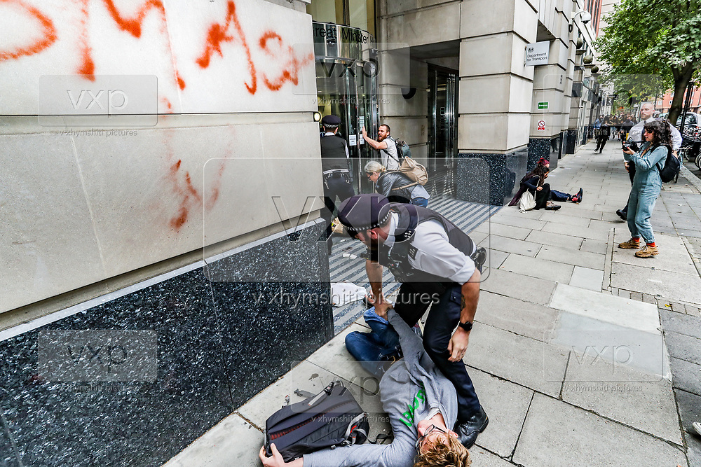 A police officer intervenes as a member of Extinction Rebellion activists group attempts to spray a message outside Department for Transport entrance, meanwhile other activists pelted red colour the building of Department for Transport's main entrance in Horseferry Road, and some others glued themselves outside DPT in central London on Friday, Sept 4, 2020. There are other Extinction Rebellion protests ongoing in London. Environmental nonviolent activists group Extinction Rebellion enters its 4th day of continuous ten days protests to disrupt political institutions throughout peaceful actions swarming central London into a standoff, demanding that central government obeys and delivers Climate Emergency bill. (VXP Photo/ Vudi Xhymshiti)
