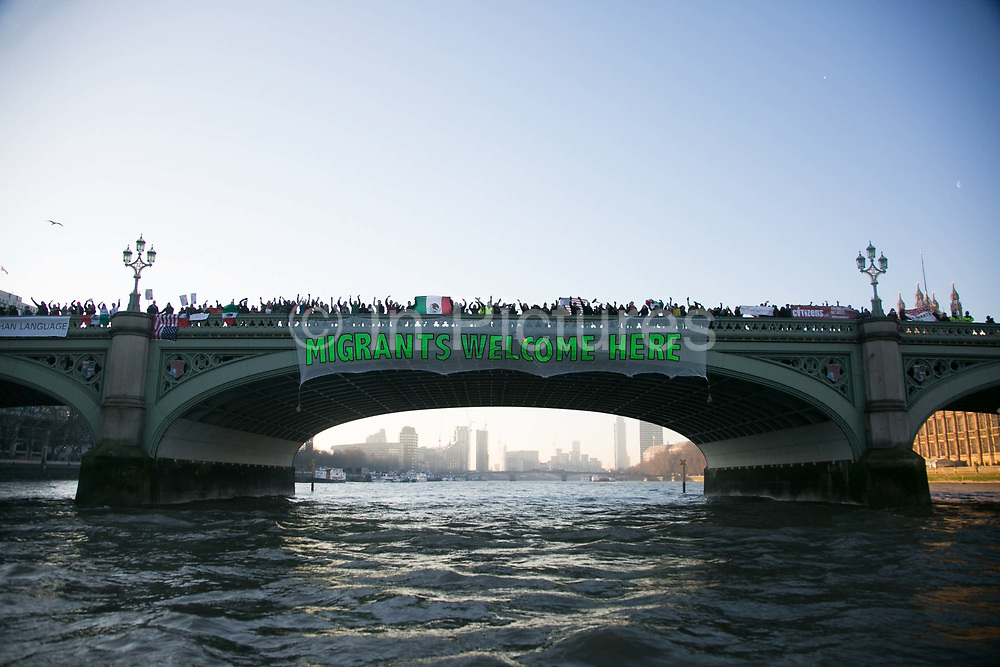 Banners were dropped on bridges crossing the Thames in protest against the inauguration of Donald Trump, January 21st 2017 in London. An Migrants Welcome Here banner on Westminster Bridge. On Friday 20th January over 50 groups across the United Kingdom dropped banners from bridges as an act of defiance against Trump's inauguration. The groups, who form the 'Bridges not Walls' movement, staged their demonstration to show support for people in the USA and beyond fearing the consequences of Trump's election. <br /> <br /> In London ten iconic bridges on the Thames saw huge banners 25m long unfurled on them.