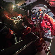 Leg 3, Cape Town to Melbourne, day 03, Pablo Arrarte  puts on his we boots while watch mate Blair Tuke gets ready for watch on board MAPFRE. Photo by Jen Edney/Volvo Ocean Race. 16 December, 2017.