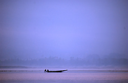 An isolated canoe makes its way across Srinagar's Dal Lake in the troubled state of Kashmir Sunday, November 18, 2001.  Kashmir's beauty is unmatched and once had a thriving tourism industry but because of the war, it has come to a virtual and complete halt.  The war in Kashmir has been going on since 1989 when militant organizations chose to fight for secession from India and now the war in Afghanistan  has made the region even more volatile . (Photo by Ami Vitale/Getty Images)