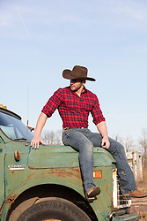 cowboy sitting on an old truck