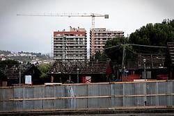 Potenza (PZ), 23-11-2010 ITALY - Il quartiere Bucaletto. Bucaletto è un quartiere popolare della periferia est di Potenza. Fu progettato all'indomani del terremoto dell'Irpinia del 23 novembre 1980, per risolvere i problemi delle famiglie sfollate a causa dei crolli di alcune abitazioni della città, difatti è caratterizzato dalla presenza di abitazioni singole, in prefabbricati..Nella Foto: Alcuni moduli abitativi in legno in corso di demolizione e sullo sfondo le due torri di edilizia popolare in costruzione.