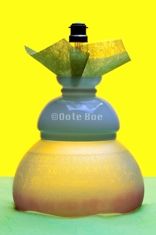 antique lamp shades with light bulb objects stacked on top of each other on yellow green background