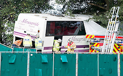 © London News Pictures. 11/09/2012. Hindhead, UK . Fire crews and police at the scene of a fatal bus crash on the north bound A3 motorway near Hindhead Tunnel, Hindhead, Surrey on September 11, 2012.Three people were killed and a number of others seriously injured when a coach carrying overturned after crashing into a tree. Photo credit: Ben Cawthra/LNP