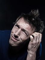 studio portrait on black background of a funny expressive caucasian man puckering hesitant