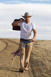 rugged good looking cowboy carrying a bag over his shoulder while walking on a dirt road in New Mexico