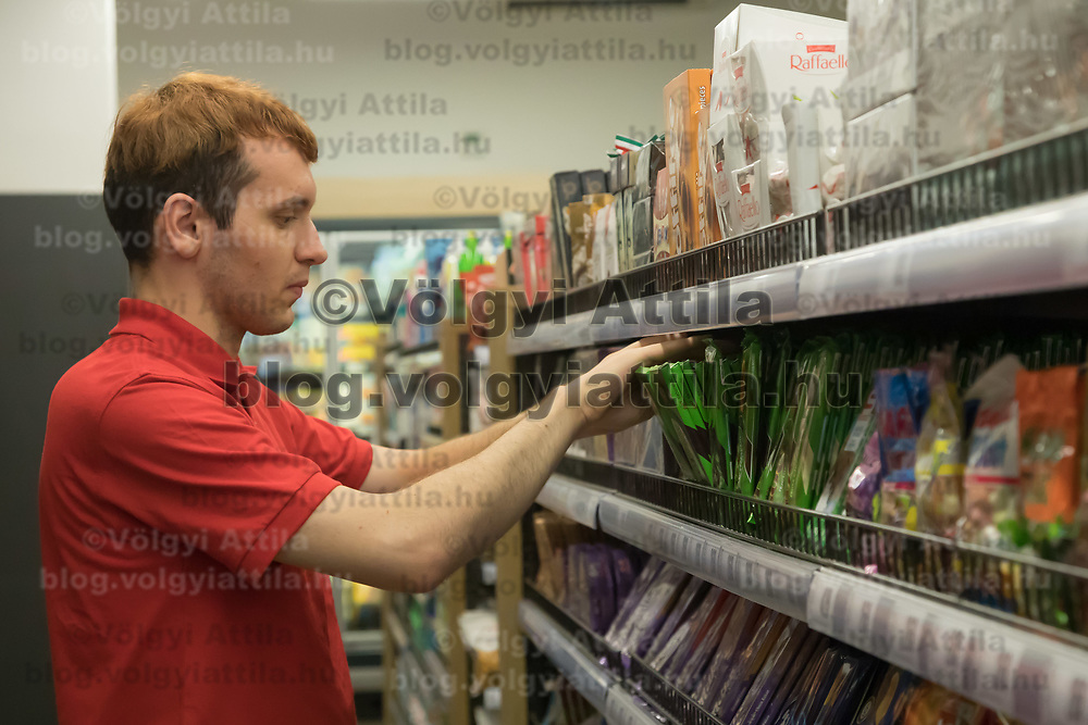 Salesman adjusts chocolate products on the selves before the official opening ceremony of a new Spar food shop in downtown Budapest, Hungary on Aug. 22, 2018. ATTILA VOLGYI