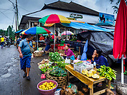 04 AUGUST 2017 - PAYANGAN, BALI, INDONESIA: A man walks past produce venders in the local market in Payangan, about 45 minutes from Ubud. Bali's local markets are open on an every three day rotating schedule because venders travel from town to town. Before modern refrigeration and convenience stores became common place on Bali, markets were thriving community gatherings. Fewer people shop at markets now as more and more consumers go to convenience stores and more families have refrigerators.      PHOTO BY JACK KURTZ