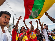 23 JUNE 2016 - MAHACHAI, SAMUT SAKHON, THAILAND: Burmese migrant workers wave a Burmese flag while they wait for Aung San Kyii to arrive in Samut Sakhon, a province south of Bangkok. Tens of thousands of Burmese migrant workers, most employed in the Thai fishing industry, live in Samut Sakhon. Aung San Suu Kyi, the Foreign Minister and State Counsellor for the government of Myanmar (a role similar to that of Prime Minister or a head of government), is on a state visit to Thailand. Even though she and her party won the 2015 elections by a landslide, she is constitutionally prohibited from becoming the President due to a clause in the constitution as her late husband and children are foreign citizens        PHOTO BY JACK KURTZ