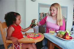 Teenage mother helping young daughter sitting in high chair to pour orange juice from carton into plastic beaker,