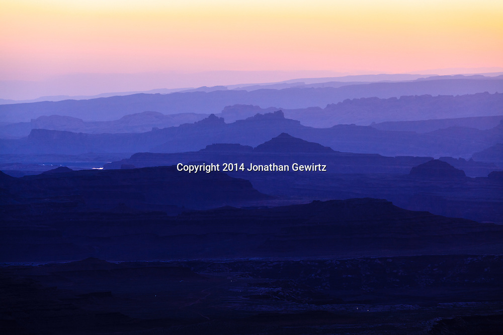 The brightening morning sky silhouettes distant ridges beyond Buck Canyon and the White Rim mesa in Canyonlands National Park, Utah.<br /> <br /> WATERMARKS WILL NOT APPEAR ON PRINTS OR LICENSED IMAGES.<br /> <br /> Licensing: https://tandemstock.com/assets/30282509