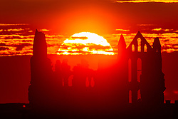 © Licensed to London News Pictures. 16/09/2021. Whitby UK. The sun rises this morning behind the Gothic ruins of Whitby Abbey on the Yorkshire coast. Photo credit: Andrew McCaren/LNP