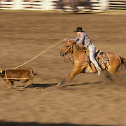 Rodeo, cowboys in team calf roping contest, Wilsall rodeo, Crazy Mountains offer backdrop. Montana.