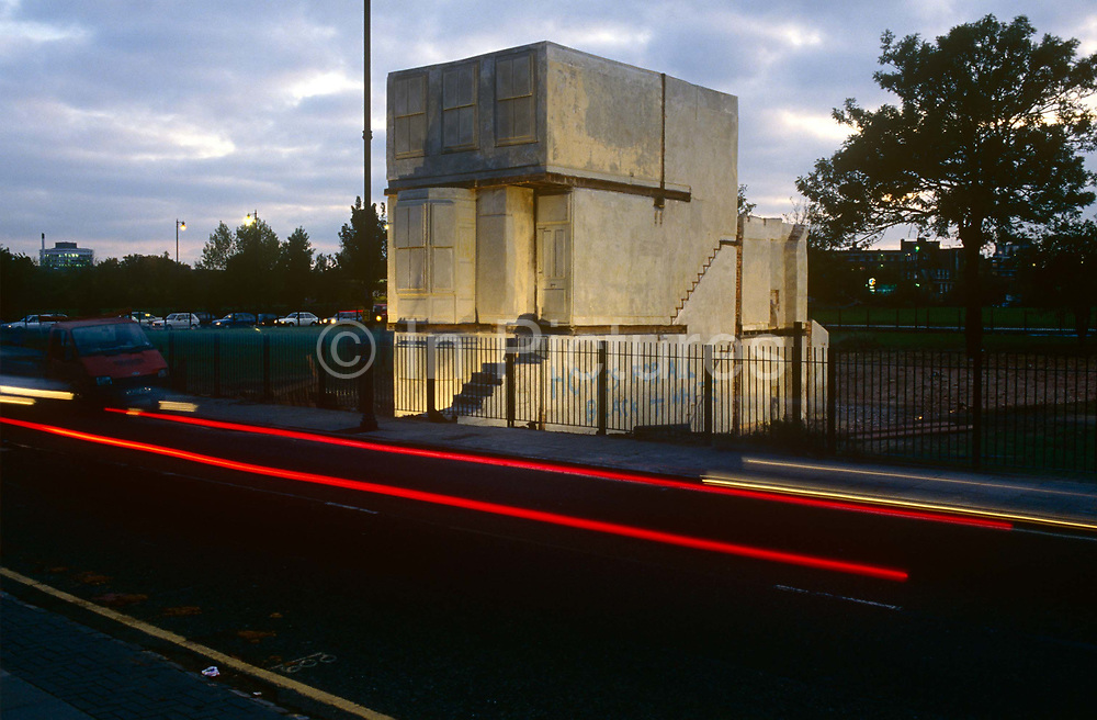 As traffic zooms past, the art installation called House stands alone on a now-empty and house-less East London street, on 2nd December 1993, in London, England. The contours of the structure have been inverted to reveal an inside-out version of the original building. It is a concrete cast of the inside of an entire Victorian terraced house completed in autumn 1993 and exhibited at the location of the original property -- 193 Grove Road -- in East London all the houses in the street had earlier been knocked down by the council. Created by the artist Rachel Whiteread CBE born 1963 this is her best-known sculpture. It won her the Turner Prize the first woman to do so for best young British artist in 1993 before being controversially demolished by the council in January 1994.