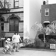 A mother walks with her son as he rides a bicycle on the sidewalk.
