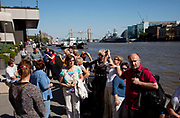 Large group of tourists listens to a tour guide along the River Thames on the north side looking towards Tower Bridge.