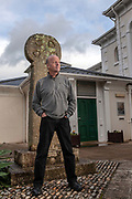 Novelist, author and journalist Jim Crace stands by the Celtic Cross at the Penlee House Gallery, Penzance, United Kingdom.