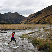 A Runner crosses  Moke Creek on the Ben Lomond High Country Station during the Pure South Shotover Moonlight Mountain Marathon and trail runs. Moke Lake, Queenstown, New Zealand. 4th February 2012. Photo Tim Clayton