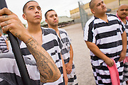 """17 JULY 2006 - PHOENIX, AZ: Inmates stand at attention during the National Anthem in """"Tent City"""" in the Maricopa County Jail in Phoenix, AZ. There are about 650 inmates living in the tents. Maricopa County Sheriff Joe Arpaio recently started playing the Star Spangled Banner and God Bless America twice a day in the county jails. Inmates are encouraged, but not forced, to stand at attention with their hands over their hearts, when the music is played. When asked about the new policy Arpaio said, """"Our men and women are fighting and dying for our country in Iraq and that's the least these inmates can do."""" In 2011, the US Department of Justice issued a report highly critical of the Maricopa County Sheriff's Department and the jails. The DOJ said the Sheriff's Dept. engages in widespread discrimination against Latinos during traffic stops and immigration enforcement, violates the rights of Spanish speaking prisoners in the jails and retaliates against the Sheriff's political opponents.      PHOTO BY JACK KURTZ"""