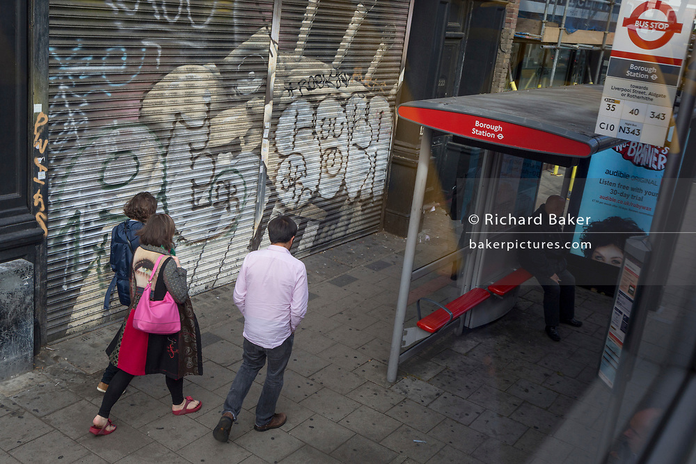 A woman walks past a bus stop at Borough Station with an ad of a female face, wearing a jacket with an eye on her back, on 11th October 2018, in London England.